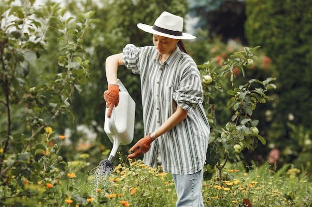 Jardinagem no verão. mulher regando flores com um regador. menina com um chapéu. Foto gratuita