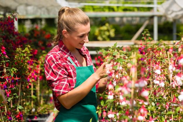 Jardineiro feminino no mercado jardim ou viveiro Foto Premium