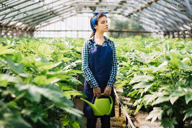 Jardineiro feminino segurando o regador com plantas que crescem em estufa Foto gratuita