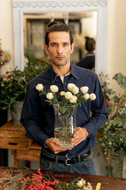 Jardineiro homem com cabelos compridos, segurando flores Foto gratuita