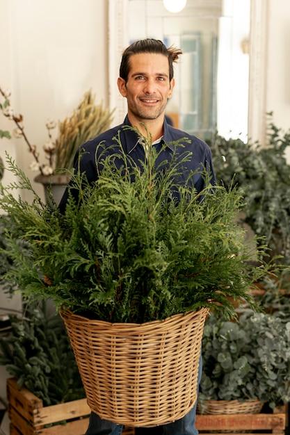 Jardineiro homem com cabelos compridos, segurando uma cesta com folhas Foto gratuita