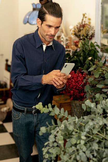 Jardineiro homem com cabelos longos, fotografando as plantas Foto gratuita