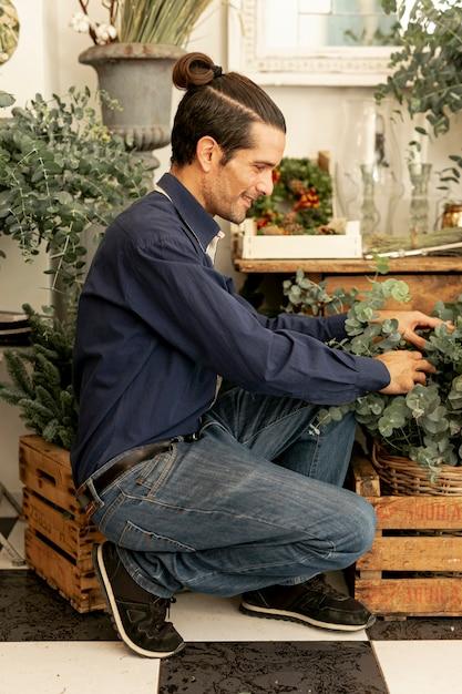 Jardineiro homem com cabelos longos, organizando as plantas Foto gratuita