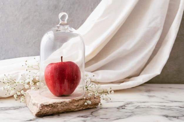 Jarra com maçã e flores ao lado Foto gratuita