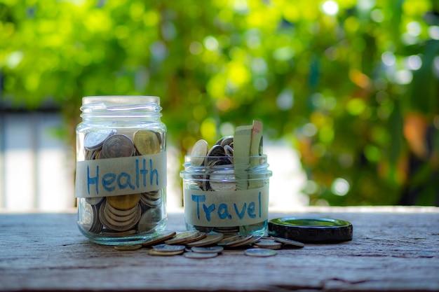 Jarra de dinheiro com moedas na mesa de madeira, saúde e conceito de viagens Foto Premium