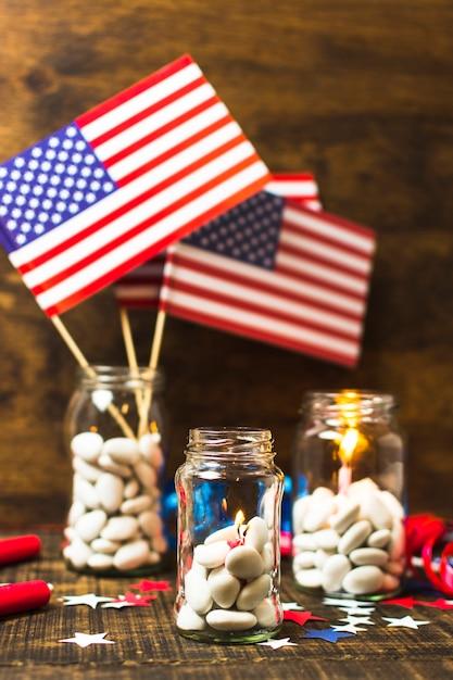 Jarra de doces branco com velas acesas e bandeira eua na mesa de madeira Foto gratuita