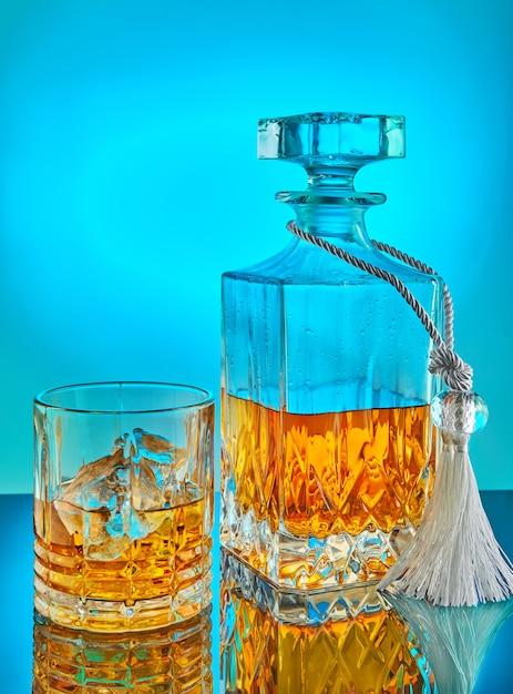 Jarra de vidro e cristal quadrado com uísque escocês ou conhaque em um fundo gradiente azul com reflexão Foto Premium