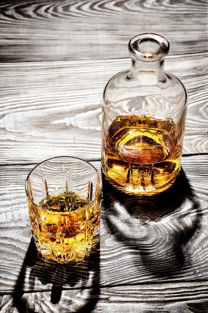 Jarra de vidro e um copo de conhaque envelhecido em uma mesa de madeira Foto Premium