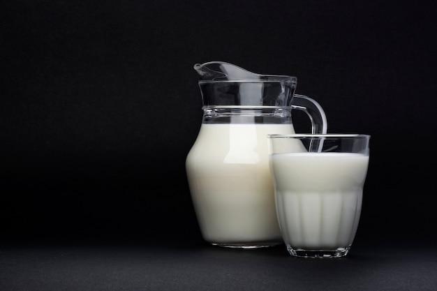 Jarra e copo de leite isolado no preto com espaço de cópia de texto, conceito de produtos lácteos Foto Premium