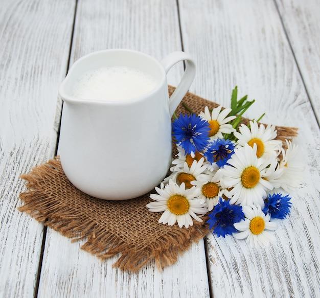 Jarro com leite e flores silvestres Foto Premium