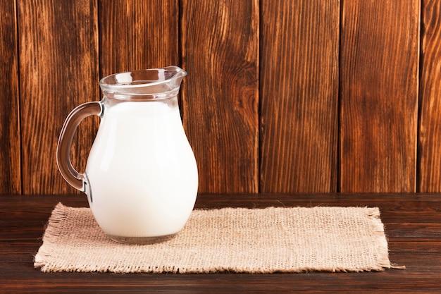 Jarro de leite fresco na mesa de madeira Foto gratuita