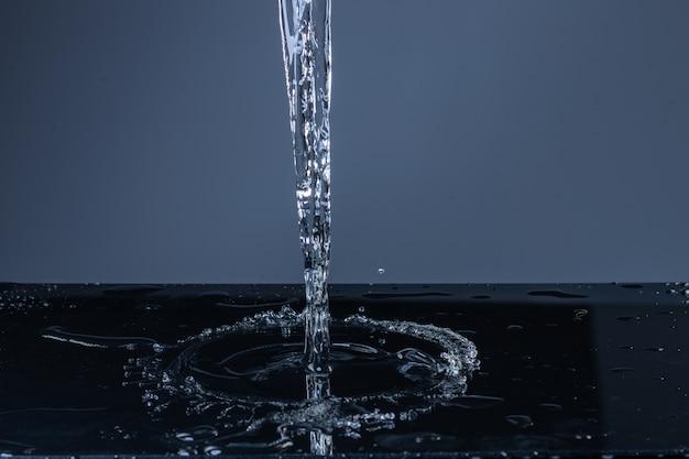 Jato de água limpa caindo em uma superfície preta Foto Premium