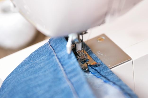 Jeans de costura com máquina de costura. reparação de jeans por máquina de costura. Foto Premium