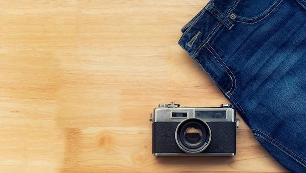 Jeans e câmeras retro deite no chão de madeira Foto Premium