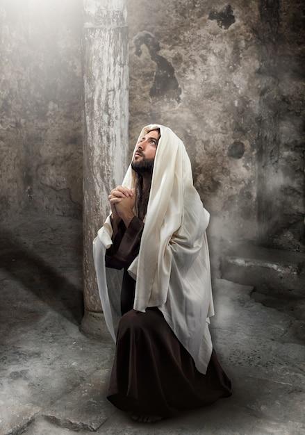 Jesus se ajoelha em oração Foto Premium