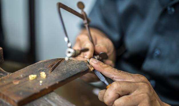 Joalheiro tailandês, lida com joias e pedras preciosas na oficina, processo de fabricação de joias, close-up Foto gratuita