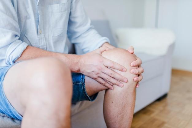 Joelho guardando paciente masculino maduro na dor. Foto Premium