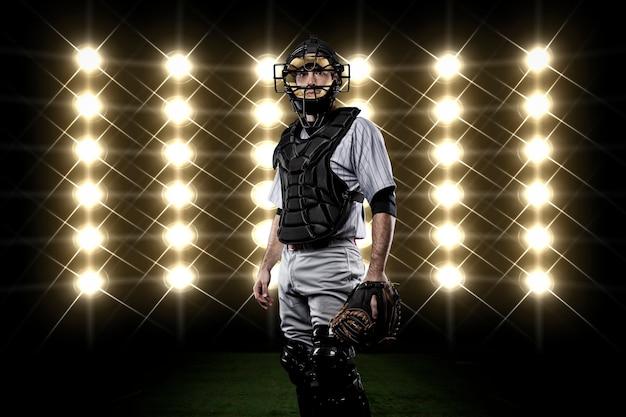 Jogador catcher na frente das luzes. Foto gratuita