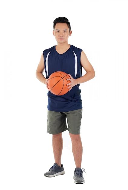 Jogador de basquete asiático no activewear em pé contra um fundo branco Foto gratuita