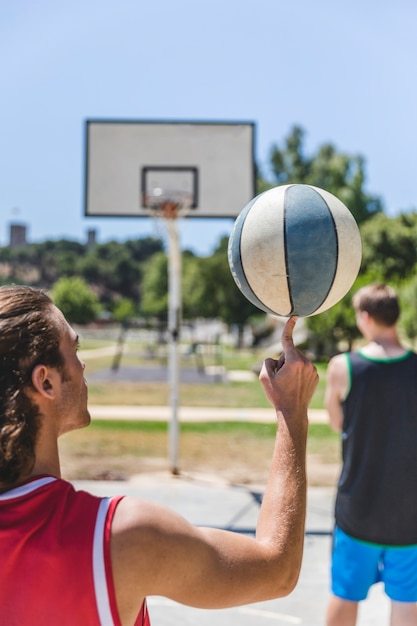 Jogador de basquete, girando a bola no dedo Foto gratuita