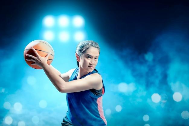Jogador de basquete menina asiática animado defendendo a bola do adversário na quadra de basquete Foto Premium