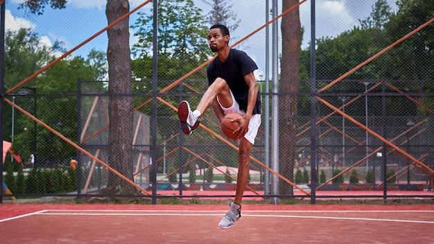 Jogador de basquete negro jogando no campo Foto Premium