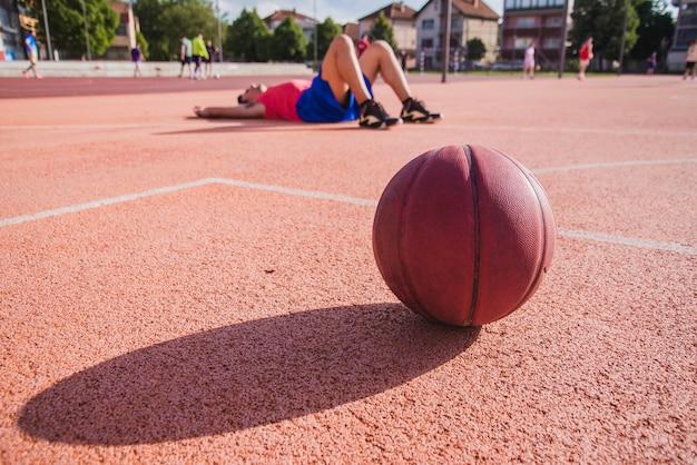 Jogador de basquete no chão com bola em primeiro plano Foto gratuita