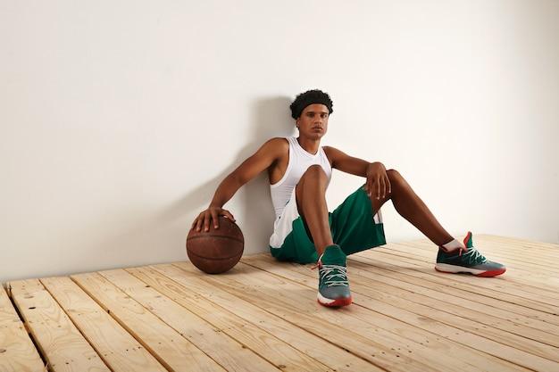 Jogador de basquete preto cansado e pensativo em outift de basquete verde e branco, sentado no chão de madeira clara, descansando a mão em uma bola de basquete marrom grunge Foto gratuita