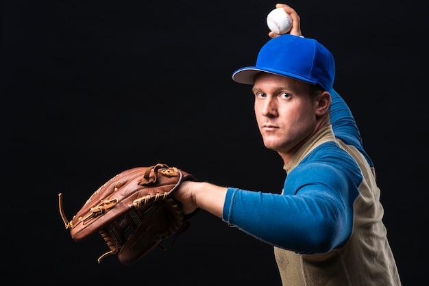 Jogador de beisebol com luva jogando bola Foto gratuita