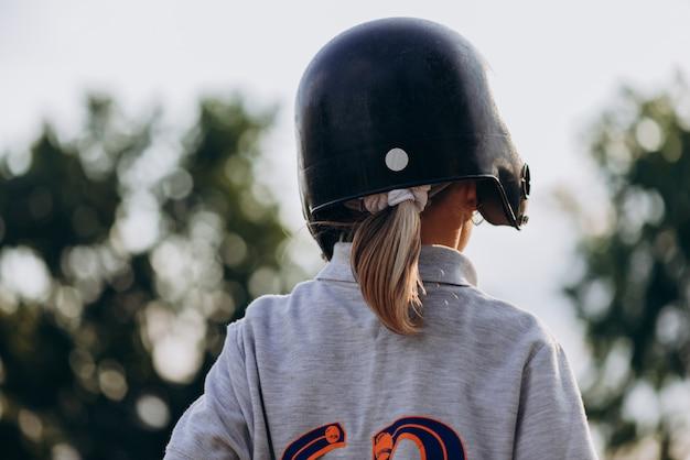 Jogador de beisebol em um capacete indolor vira as costas para a câmera Foto Premium