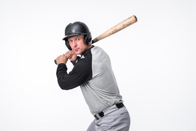 Jogador de beisebol posando no capacete com bastão Foto gratuita
