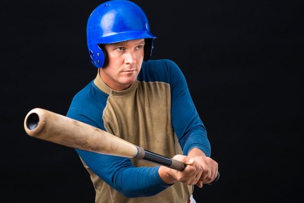 Jogador de beisebol, segurando o bastão e desviar o olhar Foto gratuita