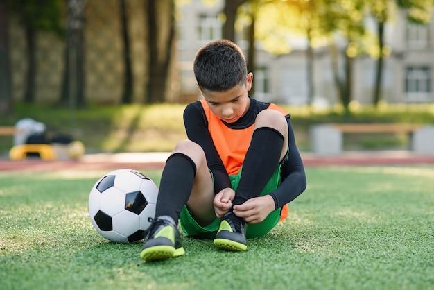 Jogador de futebol adolescente no campo de esporte ao ar livre, amarrando o cadarço nas botas. Foto Premium