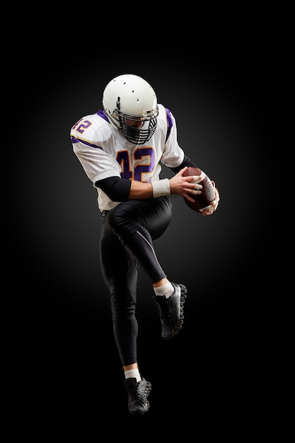 Jogador de futebol americano em um salto com uma bola em um preto Foto Premium