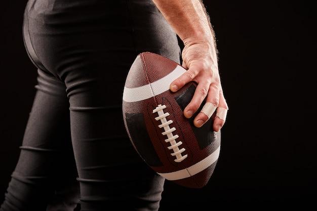 Jogador de futebol americano, segurando a bola contra o céu sombrio Foto Premium