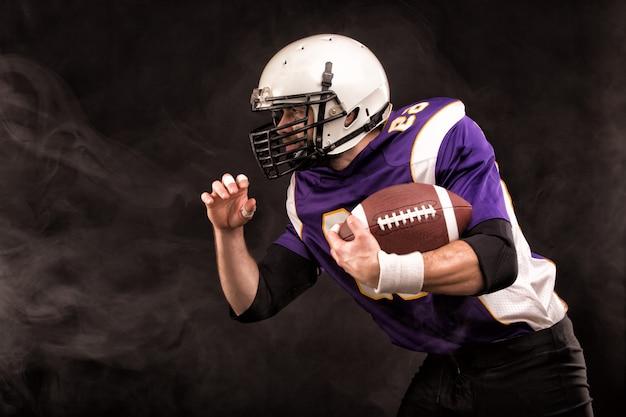 Jogador de futebol americano, segurando a bola nas mãos. o conceito de futebol americano, motivação, cópia espaço Foto Premium
