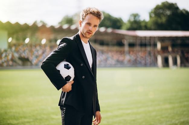 Jogador de futebol bonito no estádio em terno de negócio Foto gratuita