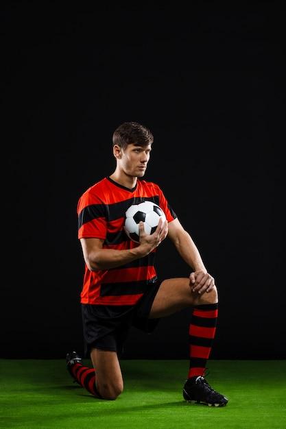 Jogador de futebol com bola em pé no joelho, jogar futebol Foto gratuita