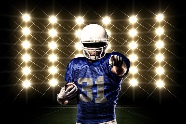 Jogador de futebol com uniforme azul na frente das luzes Foto gratuita