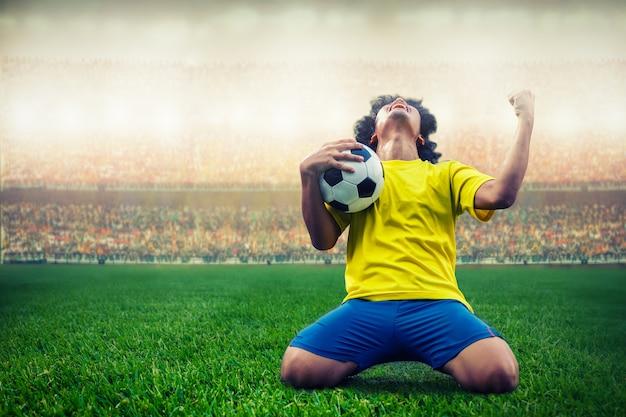 Jogador de futebol de futebol amarelo comemorando seu gol no estádio Foto Premium