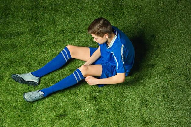 Jogador de futebol de menino sentado na grama verde Foto gratuita