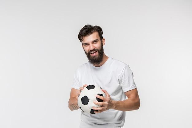 Jogador de futebol jovem com bola na frente da parede branca Foto gratuita