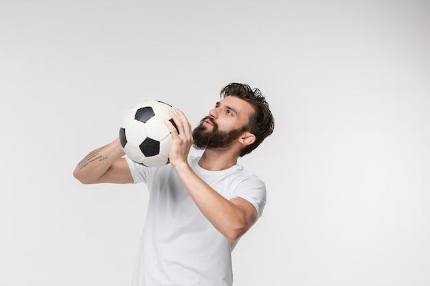 Jogador de futebol jovem com bola na frente de branco Foto gratuita