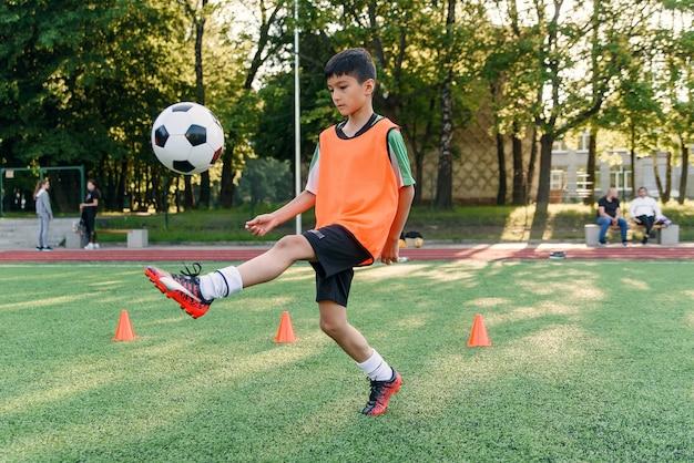 Jogador de futebol motivado enfia a bola de futebol na perna. Foto Premium
