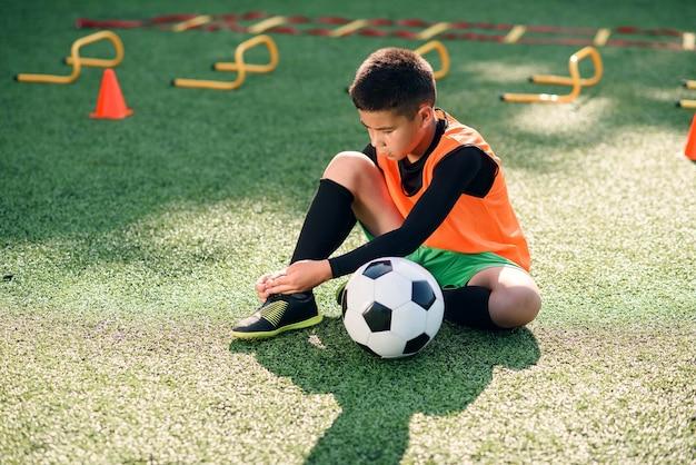 Jogador de futebol no campo de esporte ao ar livre e amarrando o cadarço nas botas. Foto Premium