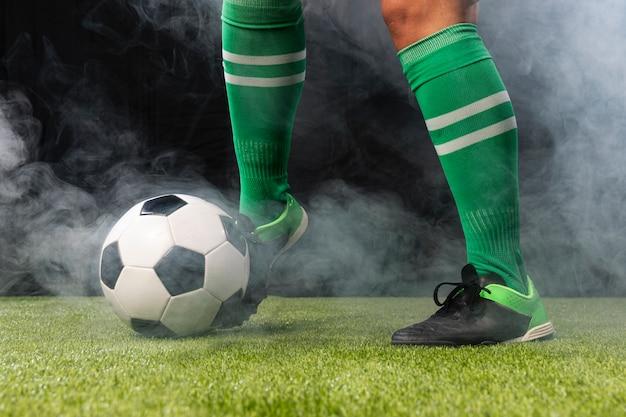 Jogador de futebol no sportswear com bola de futebol Foto gratuita
