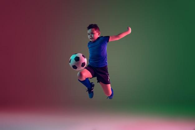 Jogador de futebol ou futebol masculino adolescente, menino em fundo gradiente na luz de neon - movimento, ação, conceito de atividade Foto gratuita