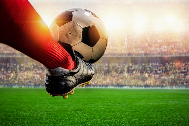 Jogador de futebol vermelho chutando a bola no estádio Foto Premium