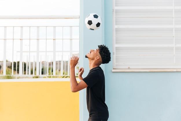 Jogador de futebol vomitando bola na varanda Foto gratuita