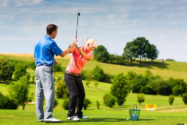 Jogador de golfe feminino jovem em curso Foto Premium